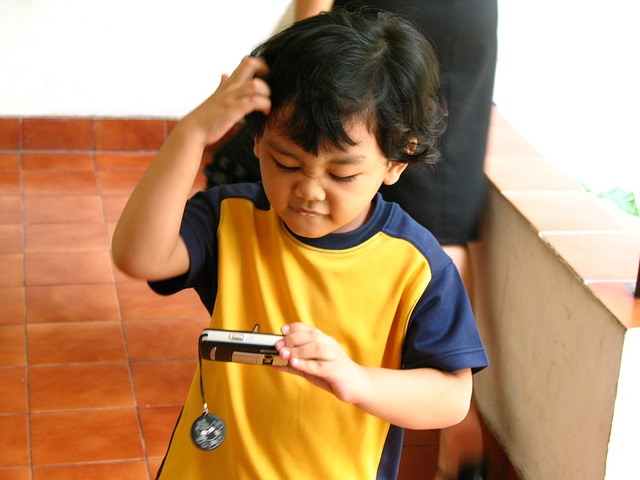 Child scratching head, looking confused, at a camera